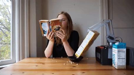 Анимация Девушка читает книгу за столом, робот пытается приготовить завтрак: разливает по столу молоко и рассыпает хлопья