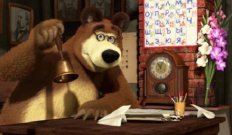 Анимация Медведь в очках звонит в колокольчик, на столе бумажный кораблик, часы, букет цветов и на стене вист азбука, мультфильм Маша и медведь