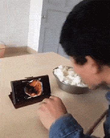 Анимация Парень ест простой рис и для поднятия аппетита смотрит на смартфоне фото красивых и изысканных блюд (© Anatol), добавлено: 04.06.2016 23:32