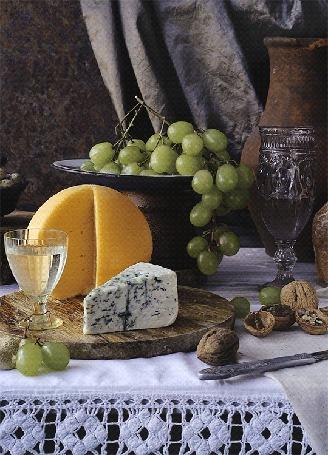 Анимация Натюрморт, состоящий из веточки винограда на тарелке, сыров, бокала с вином и орехами на столе