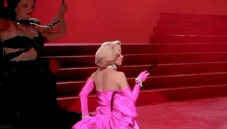 Анимация Мерилин Монро в розовом платье в окружении мужчин с сердцами