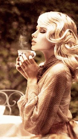 Анимация Блондинка сидит за столом и держит в руках горячий чай