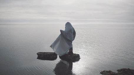 Анимация Ветер развевает белую одежду человека, стоящего в морской воде на камне, by Andrew & Carissa Gallo