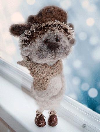 Анимация Игрушечный медвежонок в шапке-ушанке, в вязаном шарфе стоит на подоконнике