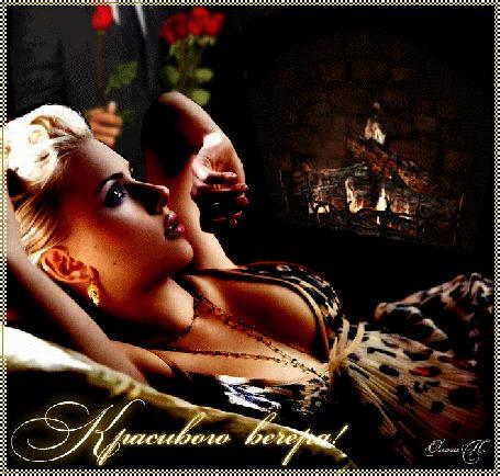 Анимация Блондинка лежит у горящего камина, в стороне виднеется мужчина в костюме с букетом роз (Уютного вечера), by Ольга П