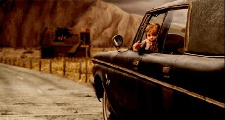 Анимация Девочка в окне автомобиля посылает воздушный поцелуй