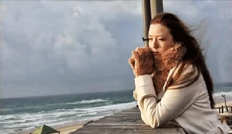 Анимация Девушка с развевающимися волосами стоит на фоне моря