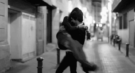 Анимация На городской улице парень кружит в танце с девушкой на руках