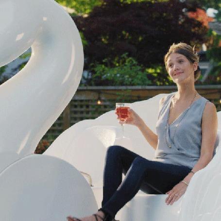 Анимация Девушка крутит педали на аттракционе в виде белого лебедя, держа в руке бокал с вином