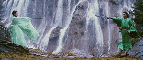 Анимация Мужчина и женщина с оружием стоят напротив друг друга на фоне водопада