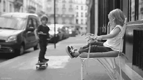 Анимация Мальчик на скейтборде подъезжает к маленькой девочке, сидящей на стульчике