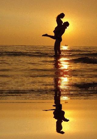 Анимация Парень стоит в море, подняв девушку, на фоне заходящего в море солнца