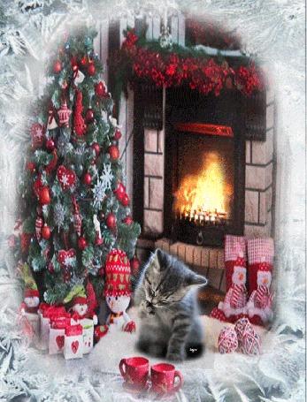 Анимация Котенок сидит около новогодней елки с подарками, перед ним красные чашки, горит камин, около которого стоят большие носки, вокруг рамка из инея