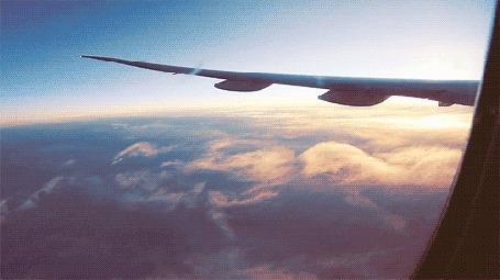 Анимация Под крылом самолета проплывают облака