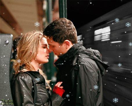 Анимация Влюбленные стоят под падающим снегом на фоне мчащегося поезда