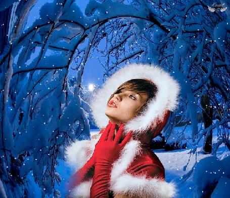Анимация На фоне зимнего леса девушка в красной одежде с белым мехом и красных перчатках подняла вверх голову, подставляя лицо под падающие с неба снежинки, by Kornet