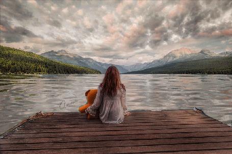 Анимация Девочка в обнимку с плюшевым медведем сидит на пирсе и смотрит на воду на фоне гор и бегущих облаков