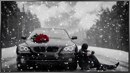 Анимация На дороге стоит машина возле которой сидит мужчина. На капоте лежат цветы, идет снег