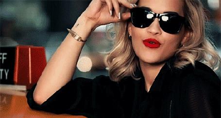 Анимация Rita Ora / Рита Ора в черных очках с красной помадой на губах, облокотившись на крышу такси, подмигивает и шлет воздушный поцелуй,(c)