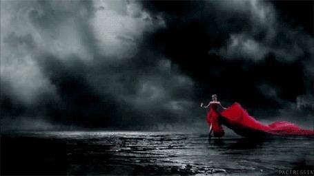 Анимация Девушка в платье с развевающимся красным шлейфом танцует на фоне облаков