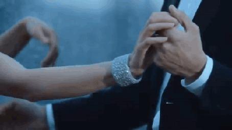Анимация Парень в строгом костюме нежно обнимает девушку в красивом вечернем платье и танцует с ней на крыше высотного дома. Над ними хмурое небо, вдали виднеются крыши других домов, высотки и свет ночного города