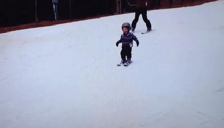 Анимация Маленький мальчик катится, стоя на лыжах, падает и продолжает катится вниз