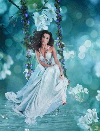 Анимация Девушка в белом платье качается на качелях платьем касаясь воды, вокруг нее белые цветы и световые блики