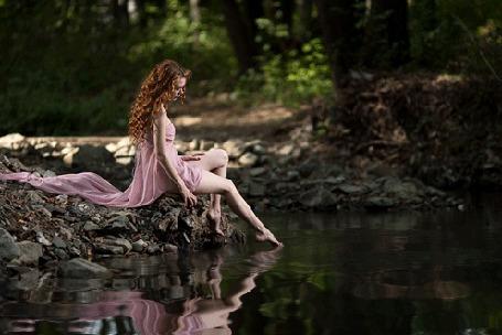 Анимация Девушка с длинными вьющимися рыжими волосами, в розовом платье, сидит на камнях в лесу у пруда, касаясь его поверхности пальцами ноги