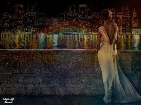 Анимация Девушка в длинном белом платье с декольте на спине стоит у парапета на набережной и любуется огнями города на другом берегу реки