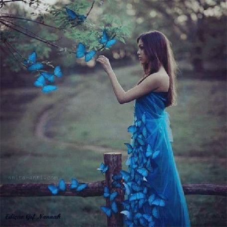 Анимация Девушка в голубом платье и в окружении голубых бабочек стоит на фоне природы
