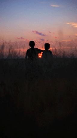Анимация Дети стоя в поле, встречая закат