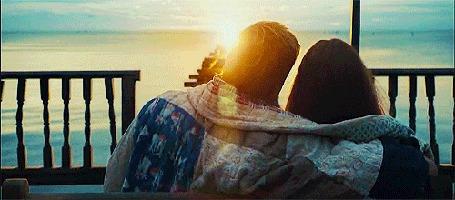 Анимация Влюбленные сидят на фоне морского заката