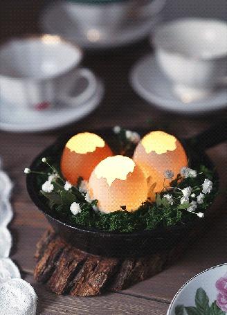 Анимация Светящиеся яйца в тарелке с цветами