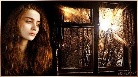 Анимация Грустная девушка стоит у окна, в котором играют лучи солнца