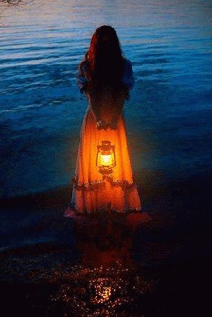 Анимация Девушка с горящим фонарем, в длинном платье, стоит в воде