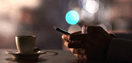 Анимация Парень держит в руках телефон перед горячей чашкой кофе