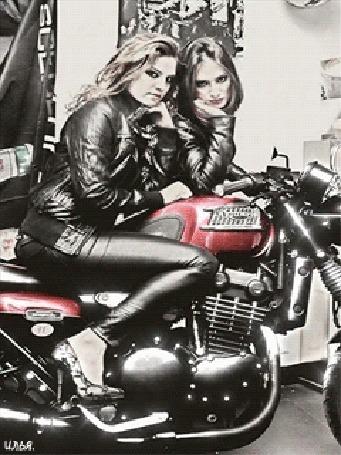 Анимация Девушка сидит на мотоцикле марки Triumph, рядом с которым стоит еще одна девушка