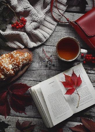 Анимация Осенний натюрморт с открытой книгой, красными листьями, круоссаном, чашкой чая, сумочкой, теплыми вещами и ягодами рябины на деревянных досках, by Daria Khoroshavina
