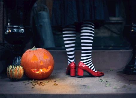 Анимация Девушка в полосатых чулках отстукивает такт ногой, рядом лежит светильник из тыквы на Хэллоуин