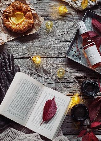 Анимация Осенний листик на открытой книге, сияющая гирлянда, печатка, бутылочка с напитком и хрустящая булочка с лимоном на дощатом столе, by Daria Khoroshavina