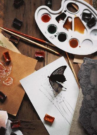 Анимация Черная бабочка машет крыльями, сидя на листе с нарисованными цветами, на столе с красками и кисточками, by Daria Khoroshavina