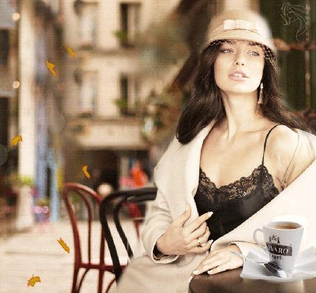 Анимация Девушка сидит на улице, за столиком с кружкой кофе на фоне городского пейзажа и падающих листьев, by Laterna