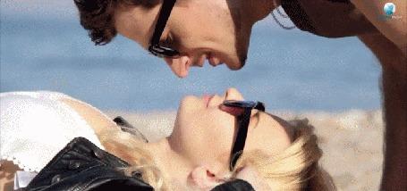 Анимация Парень целует девушку, которая лежит на берегу моря