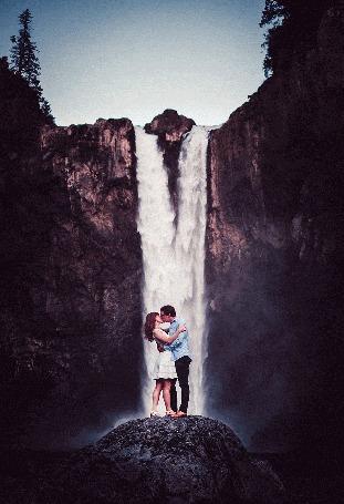 Анимация Влюбленные обнявшись стоят на фоне водопада