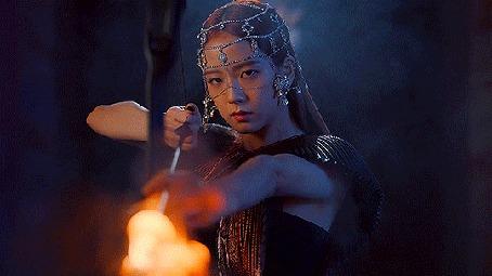 Анимация Девушка азиатской внешности с луком в руках с горящей свечой