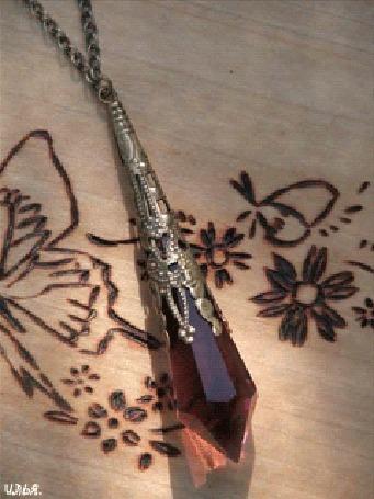 Анимация Драгоценное ожерелье красноватого оттенка, лежит на деревянном изделии, либо столе или поверхности, украшенного различными узорами и рисунками при помощи пирографа