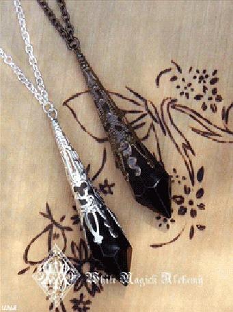 Анимация Два драгоценных ожерелья черного цветового оттенка, лежат на деревянном изделии, либо столе или поверхности, украшенного различными узорами и рисунками при помощи пирографа / White Magick Alchemy