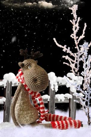 Анимация Игрушечный олень сидит на снегу у забора на фоне заснеженных деревьев (Merry christmas!) by svs