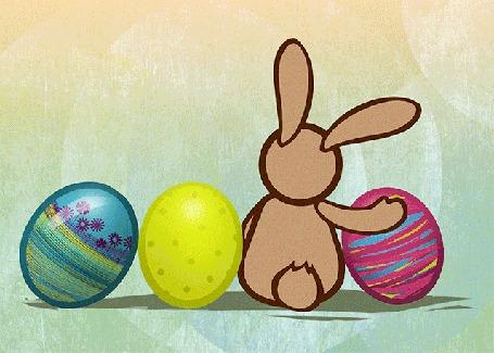 Анимация Заяц сидит рядом с пасхальными яйцами